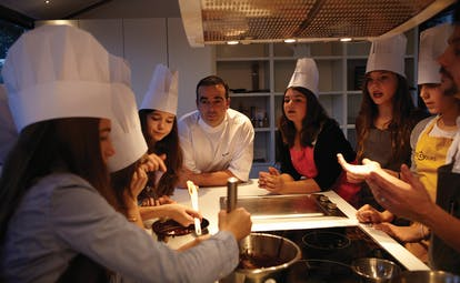 Group of ladies in chefs hats with chef, looking at people cooking