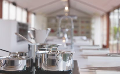 Silver pans on a stove in large white kitchen