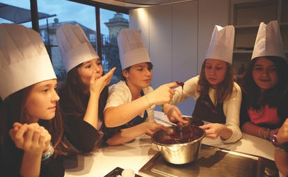 Group of ladies with chefs hats looking at cooking things