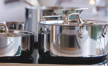 Silver pots on a hob for cookery lesson