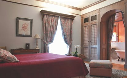 Bedroom at the Les Sources de Caudalie with large double bed, archway leading into bathroom and draping curtains