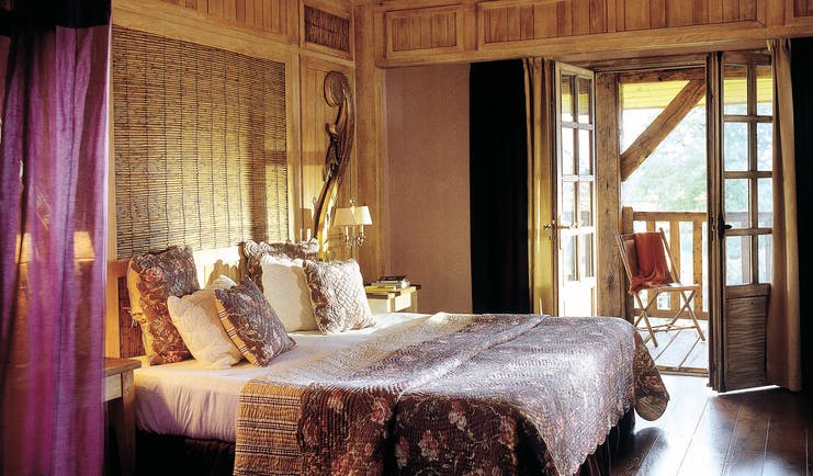 Les Sources de Caudalie suite with large double bed, wooden floors and double doors opening onto a wooden balcony