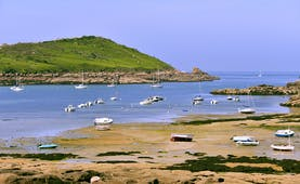 Coast with beach and boats on pink granite coast near Trebeurden