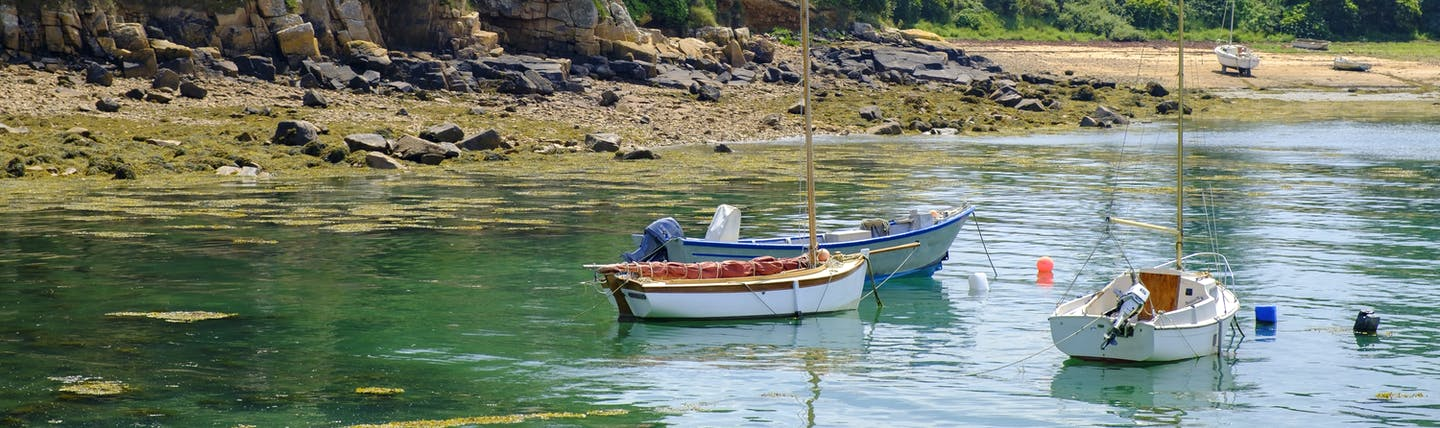 Small boats on calm water on coast with cliffs behind in Brittany