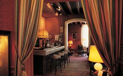 Bar with burgundy colour scheme and lamp shades around the room for light
