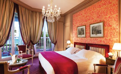 Bedroom with pink colour scheme, draping curtains, a large chandelier and double bed