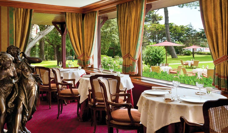 Restaurant with tables and chairs set out inside near to windows with views over the gardens
