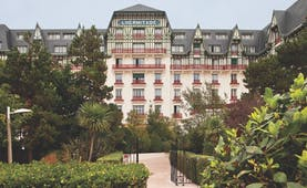 Hotel Hermitage Barriere Brittany exterior garden white building with blue tiled sign balconies and greenery