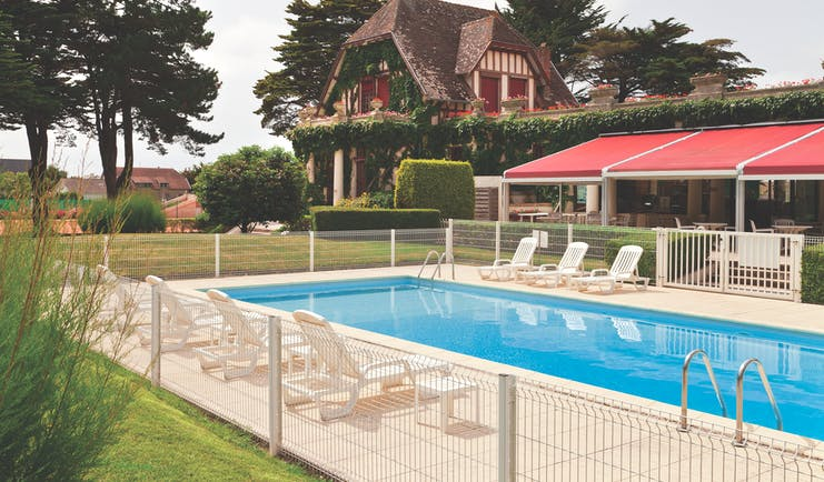 Hotel Hermitage Barriere Brittany exterior pool with loungers near an old building and a terrace area