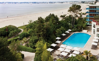 Hotel Hermitage Barriere Brittany outdoor pool facing onto the beach with sun loungers and umbrellas