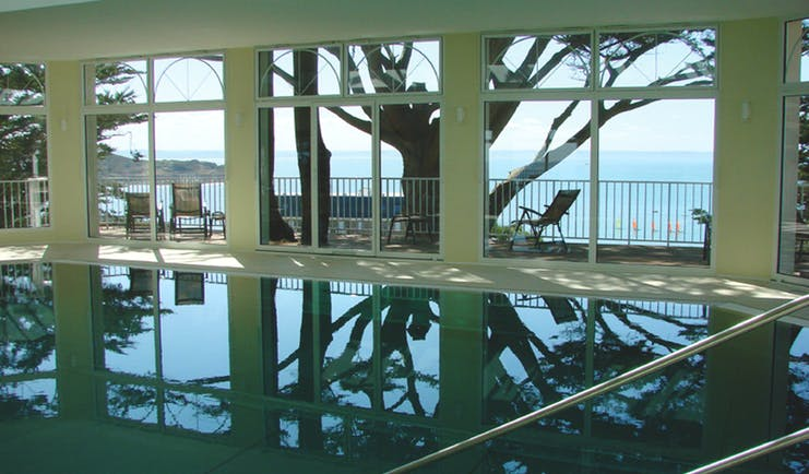 Indoor pool with window pannelled walls leading onto a balcony and looking over the sea