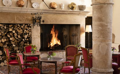 Chateau de Gilly bar with large fireplace and red chairs