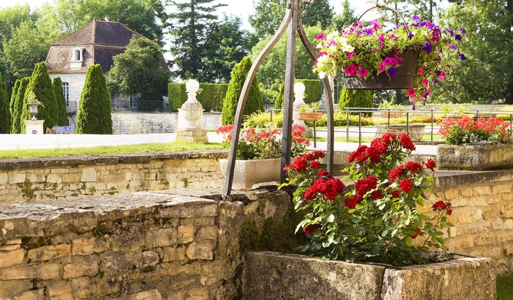 Chateau de Gilly gardens with red roses in stone tub