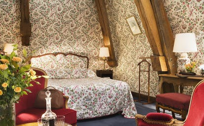 Chateau Gilly Burgundy tradition bedroom with floral wallpaper a wooden desk and an armchair