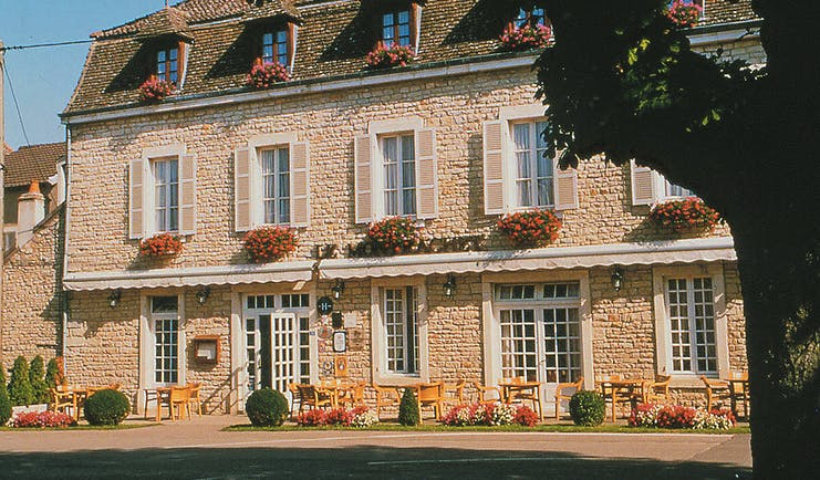 Le Montrachet Burgundy exterior stone building with shuttered windows and hanging baskets