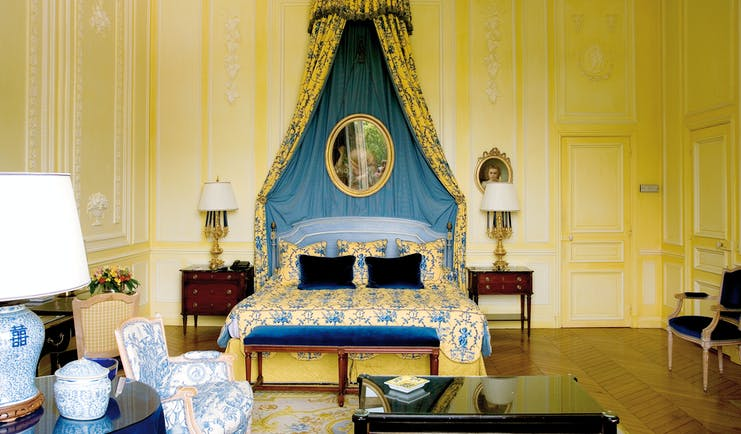 Bedroom with yellow and blue colour scheme, double bed and bed side tables with drapes