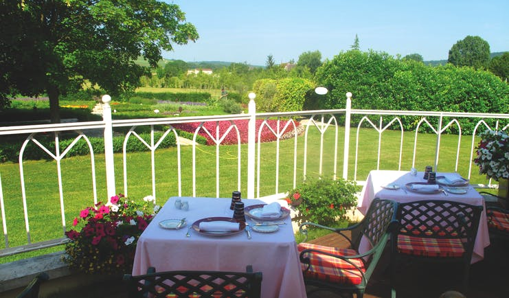 Hostellerie Briqueterie Champagne terrace outdoor dining area with two tables and flowers overlooking a garden area