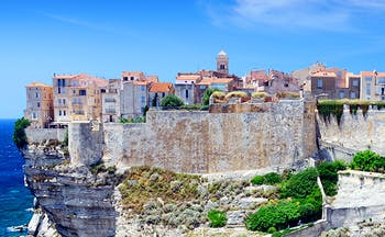 Old town and buildings fortified in pale stone on cliff above sea