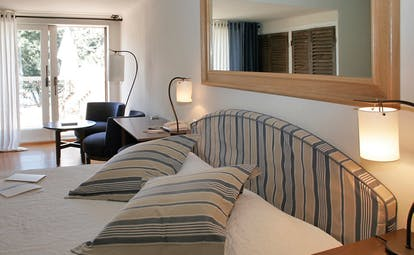 Grand Hotel de Cala Rossa Corsica Capucine room bedroom with blue and white head board and patio doors to balcony