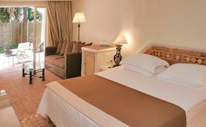 Grand Hotel de Cala Rossa Corsica eglantine room bedroom with sofa and patio access