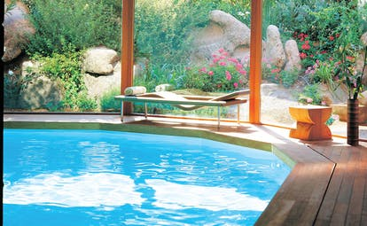 Grand Hotel de Cala Rossa Corsica indoor pool with garden view and lounger