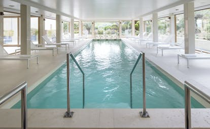 Indoor swimming pool with window pannelled walls and white sun loungers around the edge of the pool