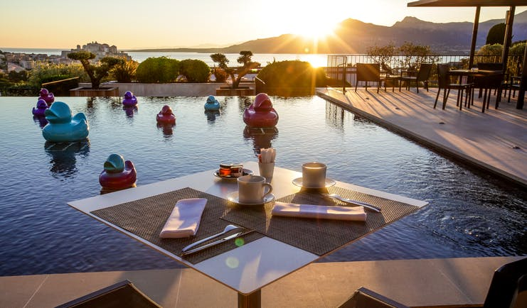 Outdoor pool with dining table set out around the edge, sun setting behind mountains in the background and ducks in the pool