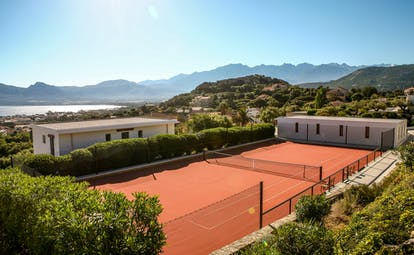 Tennis court with view of sea and mountains in the distance