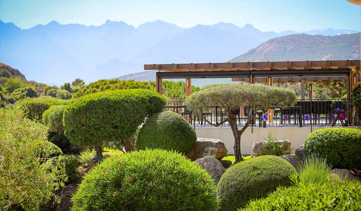 View of terrace amongst the gardens with hedges and trees in front and mountains in background