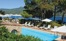 Miramar Boutique Hotel Corsica outdoor pool with sun loungers and large umbrellas