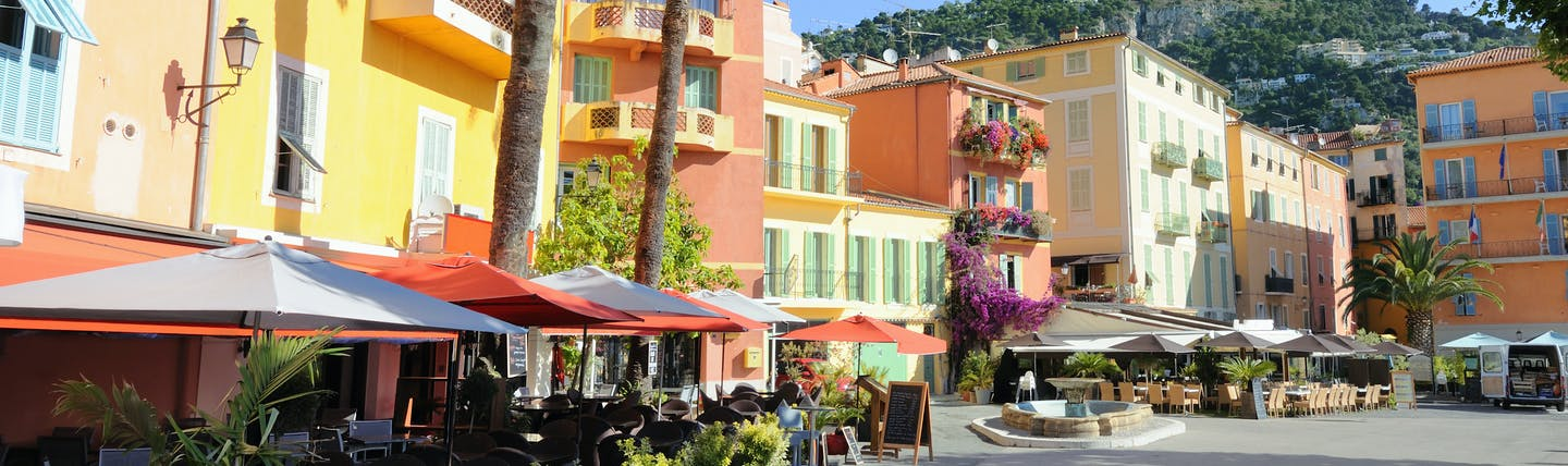 Pink and yellow houses with palmtrees lining a square in Villefranche sur Mer