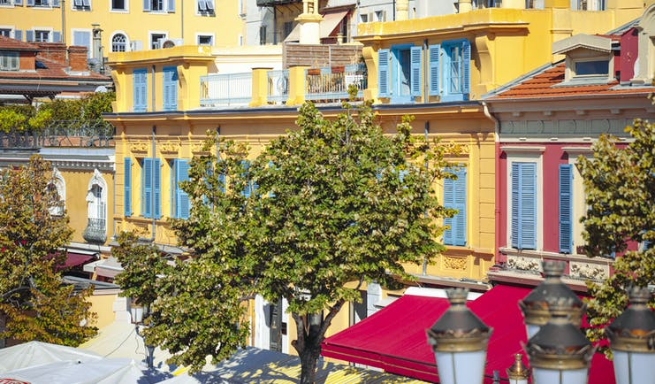 Yellow houses with blue shutters in flower market Nice