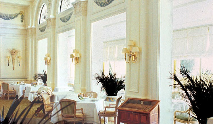 Grand Hotel du Cap Ferrat restaurant indoor dining area with large windows and plants