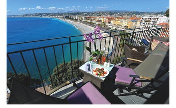 Hotel La Perouse Nice balcony overlooking the sea with two tables and chairs with a salad and flowers