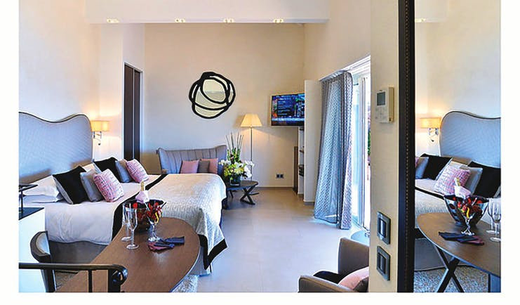 Hotel La Perouse Nice sea view bedroom with black and white mirror a sofa and a desk with wine