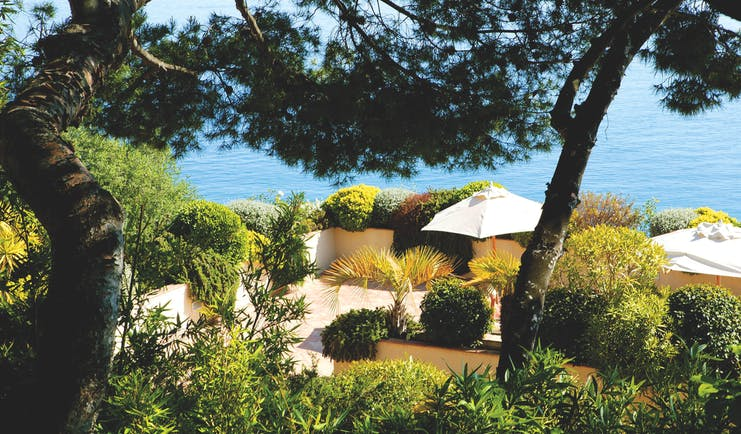 Hotel La Perouse Nice vista view of a walled patio surrounded by trees and shrubs overlooking the sea