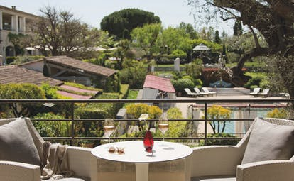 Le Mas de Pierre Cote d'Azur balcony with two chairs and a table overlooking a swimming pool