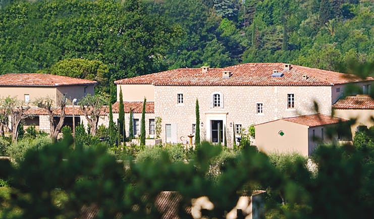 Le Mas de Pierre Cote d'Azur outside building large stone buildings with terracotta rooves in front of a wooded hillside