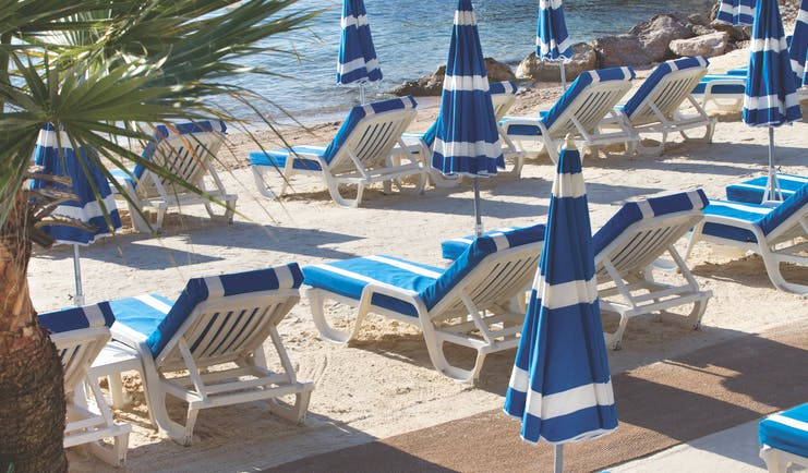 Royal Riviera Cote d'Azur beach sea blue and white sun loungers and umbrellas