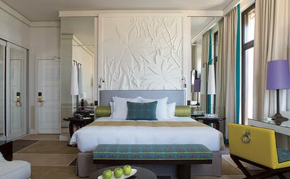 Royal Riviera Cote d'Azur junior suite bedroom with a white floral embossed wall