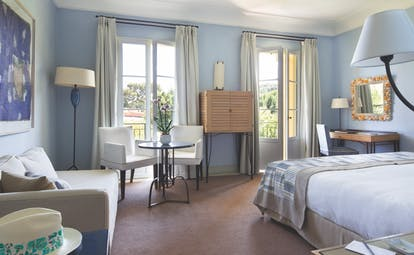 Royal Riviera Cote d'Azur deluxe bedroom with sofa table and chairs and writing desk