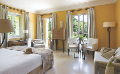 Royal Riviera Cote d'Azur orangerie deluxe yellow bedroom with sofa and armchair table and chairs and writing desk