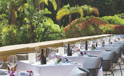 Royal Riviera Cote d'Azur garden view terrace tables with wine glasses overlooking garden and flowers