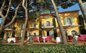 Le Mas Candille Cote d'Azur outdoor restaurant dining area in front of yellow building with green shutters