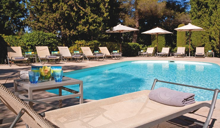 Le Mas Candille Cote d'Azur outside pool sun loungers and umbrellas