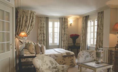 Le Saint Paul Cote d'Azur deluxe bedroom with drapes above bed with cream and grey floral pattern