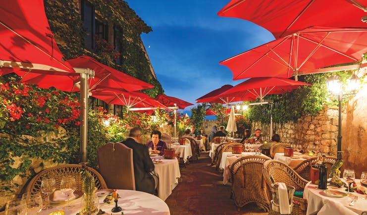 Le Saint Paul Cote d'Azur outdoor restaurant with umbrellas and red flowers