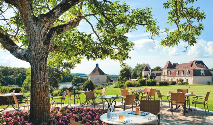 Chateau des Vigiers Dordogne brasserie chai dining area next to a tree and flower bed with pink flowers