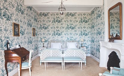 Chateau des Vigiers Dordogne deluxe blue room floral wallpaper and wooden writing bureau and fireplace