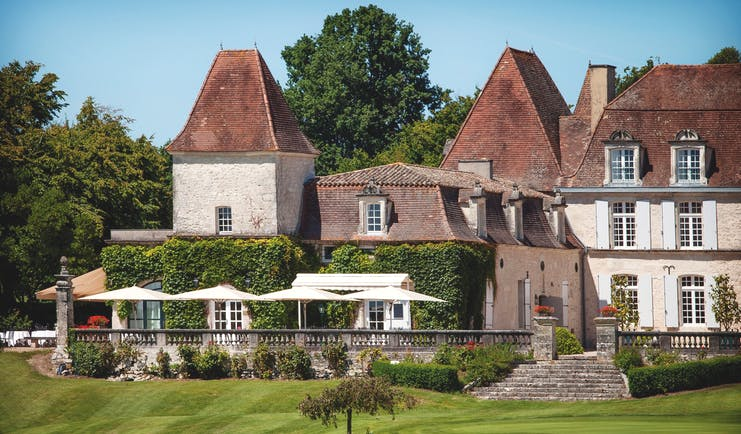 Chateau des Vigiers Dordogne outdoor large building foliage covered wall seating area with large white umbrellas